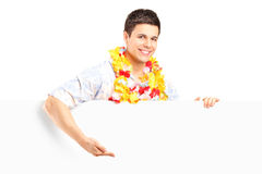 Young man with lei around his neck behind a panel Stock Image