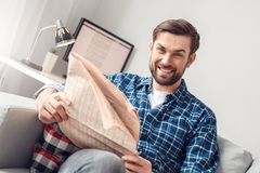 Young man leisure at home sitting holding newspaper cheerful royalty free stock image