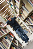 Young Man at the Library. A young man standing in the aisles of the library book shelves Royalty Free Stock Photos