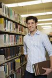 Young Man In Library. Young Man Holding Books In Library Royalty Free Stock Image
