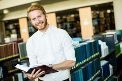 Young man in the library. Young man reading in the library Stock Photo