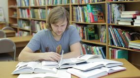 A young man in the library reads a lot of books. He s terrified by the amount of information. Student reading book. Surrounded by lot of books - I will never stock footage