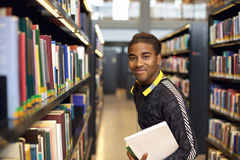Young man in library for reference books. Image of happy young man standing by book shelf in library. African american student in public library holding books stock photo