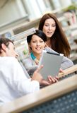 Young man at the library shows tablet to two women Royalty Free Stock Photo