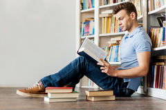 Young man in library. Side view of handsome young man reading a book while sitting on the floor and leaning at the library bookshelf Royalty Free Stock Images