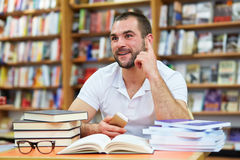 Young man in the library. Young man working and thinking in the library Royalty Free Stock Photography
