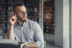 Young man in the library. Young man at work in the library royalty free stock images