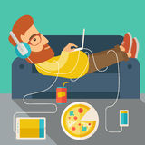 Young man lie on the sofa. A Young caucasian man with headphone lie on the sofa listening music with pizza. Contemporary style with pastel palette, soft green Stock Photography