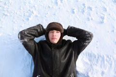 Young man lies on back on snow Royalty Free Stock Image