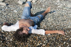 Young man lies on coastline Stock Photo