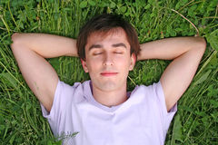Young man lies on grass head on hands closed eyes Stock Photography