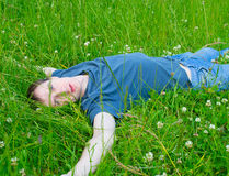 The young man lies on a green grass Royalty Free Stock Photo