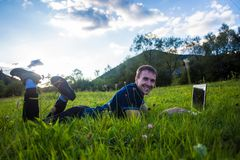 Young man lies on green grass with laptop and working Royalty Free Stock Image