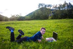 Young man lies on green grass with laptop and working Royalty Free Stock Images