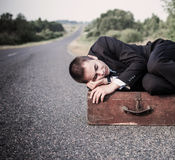 Young man lies on the old suitcase Stock Photo