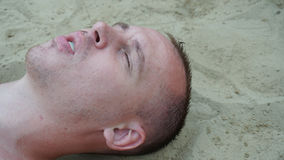 A young man lies on the sand on the beach.  Stock Photography