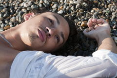 Young man lies on seacoast Royalty Free Stock Photo