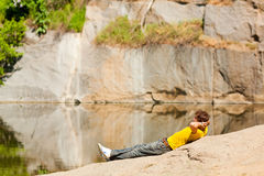 A young  man lies on the shores of Lake Stock Photography