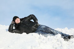 Young man lies on snow support palm Royalty Free Stock Photography