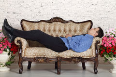 Young man lies on vintage couch and dreams Stock Photos