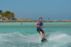 Young Man in a Life Vest Riding a Wakeboard Royalty Free Stock Photos