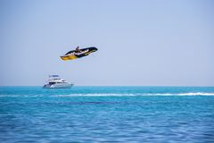 Young man in lifejackets have fun and ride a large black and yellow flying banana boat water attraction in the sea on the backgrou. Nd clear sky stock photo