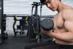 Man lift dumbbell in gym. bodybuilder male working out in fitnes. Young man lift dumbbell in gym. bodybuilder male working out in fitness center. sport guy doing Stock Photography