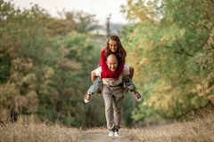 Young man lifted up girl on his back and runs on forest path. Stock Image