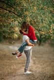 Young man lifted up girl in his hands and they kiss on walk in f Royalty Free Stock Image