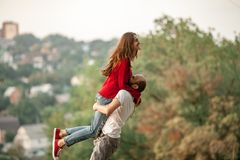 Young man lifted up girl in his hands and they laugh cheerfully. Enamored couple have fun on rest in forest. Young men lifted up girl in his hands and they laugh Royalty Free Stock Photos