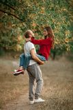 Young man lifted up girl on his hands and they smile on walk in Stock Photos