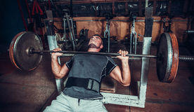 Young man lifting the barbell Stock Images