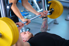 Young man lifting the barbell in gym with Royalty Free Stock Photography