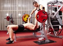 Young man lifting the barbell with help Stock Image