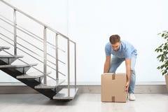 Young man lifting carton box indoors. Posture concept royalty free stock images