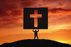 Young man lifting a crucifix on the board Stock Photography