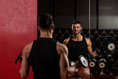 Young Man Lifting Dumbbell In Gym Stock Photo