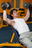 Young man lifting dumbbells in sport club. Young athlete lifting dumbbells in sport club Royalty Free Stock Images