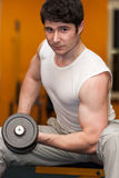Young man lifting dumbell at fitness gym Stock Photography