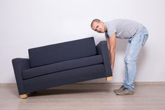 Young man lifting up sofa or couch Royalty Free Stock Photography