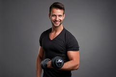 Young man lifting weight Stock Photos