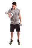 Young man lifting weights Royalty Free Stock Photos