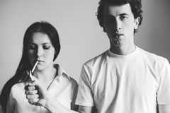 Young man light in a cigarette to a young woman. Black and white photo stock images