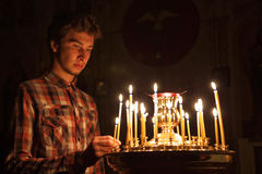 Young man lighting a candle in the church. A young man lights a candle and pray in an Orthodox church at night Stock Photography