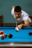 Young Man Lines Up A Shot. Young Man Lining To Hit Ball On Pool Table Royalty Free Stock Images