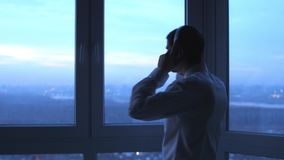 Young man listen music in headphones dances near the window and looks on night city background. 3840x2160 stock video footage