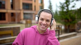 Young man listen to the music on smartphone. Young trendy man listen to music on smartphone in city park. Happy man. Listening to music. slow-motion stock video footage