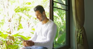 Young Man Listen To Music On Tablet Computer With Earphones Sitting One On Window Sill Looking To Tropical Garden. Slow Motion 60 stock video