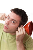 Young man listening through a funnel. Young man, holding a funnel in one arm and finger in the other one, listening stock photo