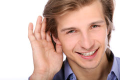 Young man listening with hand on ear Royalty Free Stock Images